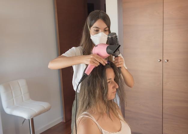 마스크 빗질 및 고객의 머리카락을 곧게 펴는 미용사. 유행성시기에 미용 세션.