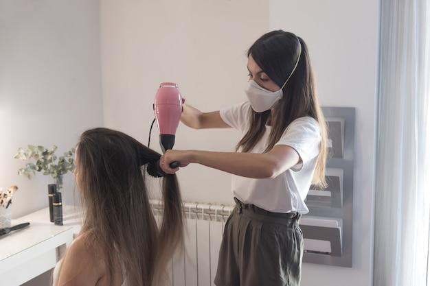 クライアントの髪をとかし、まっすぐにするマスクを備えた美容師。パンデミック時の理髪セッション。