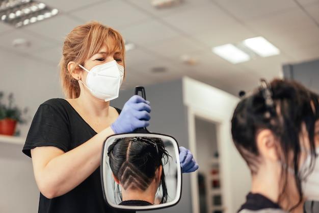 鏡でカットの結果を示すマスク付き美容師。 covid-19パンデミックにおける美容院のセキュリティ対策を再開