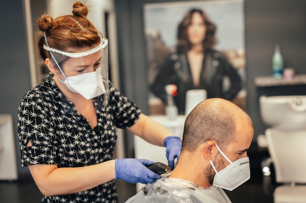 Hairdresser with security measures for the covid-19, new normality, social distance. pelura and client with mask