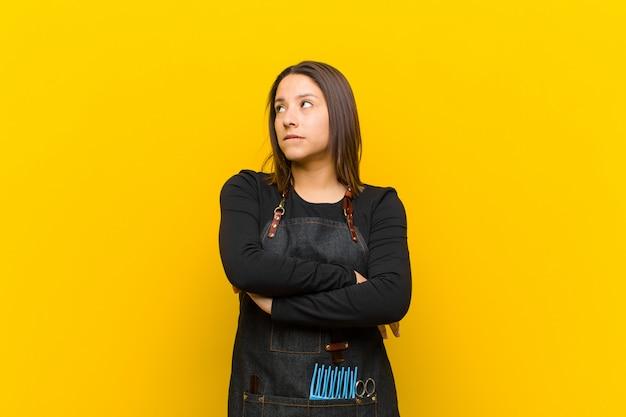 Парикмахер женщина сомневается или думает, кусая губу и чувствуя себя неуверенно и нервно, глядя, чтобы скопировать пространство на стороне на оранжевом фоне