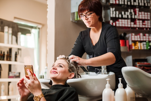 Hairdresser and woman during hair wash