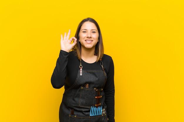 Женщина парикмахер, чувствуя себя счастливым, расслабленным и довольным, показывая одобрение жестом, улыбаясь на оранжевом фоне