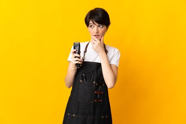 疑いを持っている黄色の背景に分離された美容師の女性
