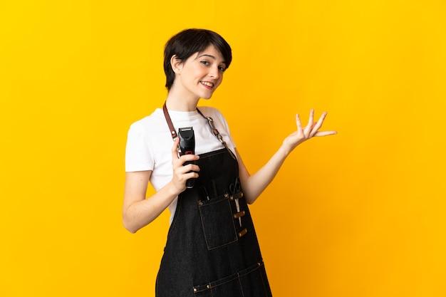 Женщина-парикмахер изолирована на желтой стене, протягивая руки в сторону, приглашая приехать