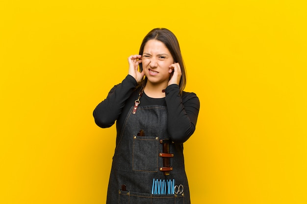 Женщина-парикмахер, выглядящая злой, подчеркнутой и раздраженной, закрывающая оба уха на оглушительный шум, звук или громкую музыку на оранжевом фоне