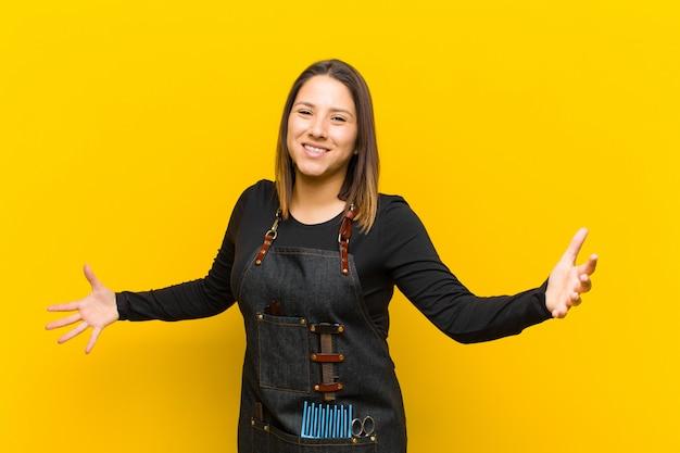 Парикмахер женщина выглядит счастливым, высокомерным, гордым и самодовольным, чувствуя себя номером один на оранжевом фоне