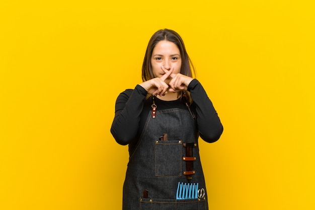 Женщина-парикмахер, выглядящая серьезной и недовольной обоими пальцами, скрещенными спереди в отторжении, просит молчания на оранжевом фоне