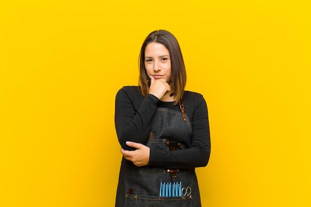 Женщина парикмахер, выглядящая серьезной, растерянной, неуверенной и вдумчивой, сомневающейся среди вариантов или вариантов на оранжевом фоне