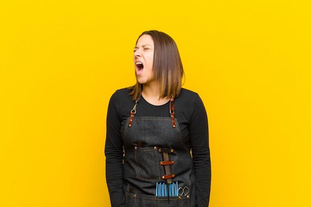 Женщина парикмахер яростно кричать, агрессивно кричать, выглядит напряженным и злой на оранжевом фоне