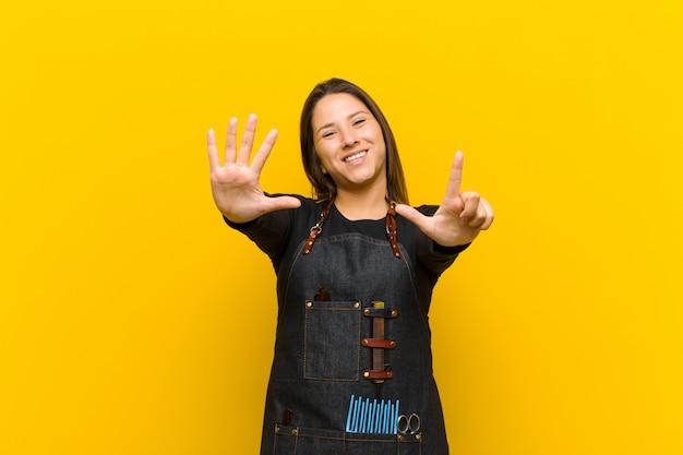 Парикмахер женщина улыбается и смотрит дружелюбно, показывая номер семь или седьмой рукой вперед, считая вниз на оранжевом фоне