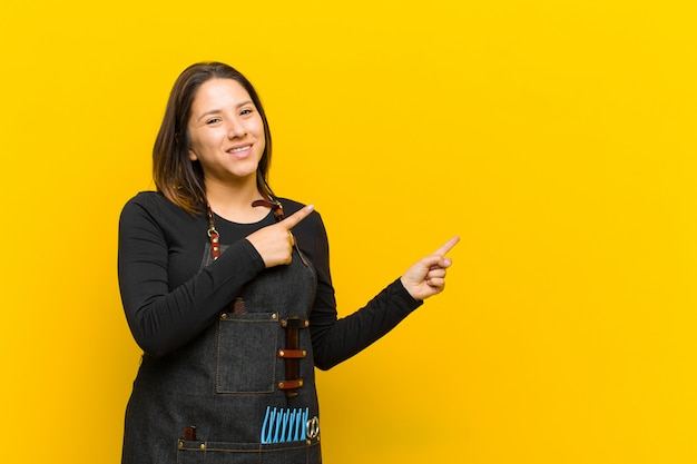 Hairdresser woman smiling happily and pointing to side and upwards with both hands showing object in copy space