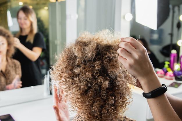 Парикмахер работает с красивой женщиной в парикмахерской. крупным планом вид руки, плойка и прибор