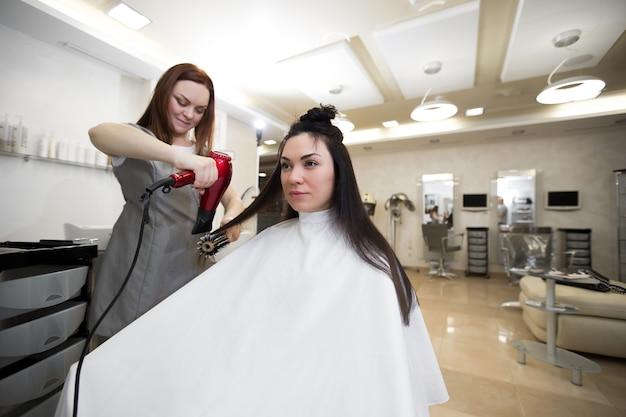 미용사는 미용실에서 고객과 함께 일합니다. 미용사는 헤어 드라이어로 젖은 머리 소녀를 건조