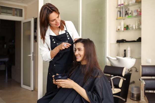 미용사는 미용실의 거울에서 여성 고객의 머리카락과 함께 작동합니다. 헤어 살롱의 스타일리스트와 클라이언트. 뷰티 사업, 전문 서비스