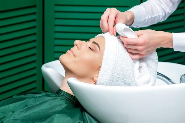 美容師がタオルで女性の髪を包みます。
