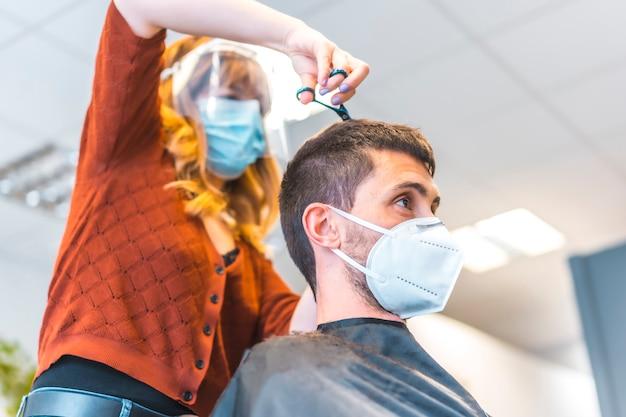コロナウイルス大流行後の美容院。フェイスマスクと保護スクリーンを備えた美容師、covid-19。社会的距離、新しい正常性。美容院で若い白人男