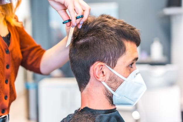 コロナウイルス大流行後の美容院。フェイスマスクと保護スクリーンを備えた美容師、covid-19。社会的距離、新しい正常性。散髪を受けて美容院で若い男