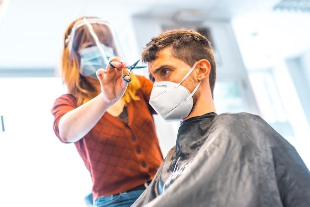 コロナウイルス大流行後の美容院。フェイスマスクと保護スクリーンを備えた美容師、covid-19。社会的距離、新しい正常性