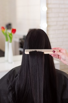 Hairdressers hand brushing long brunette hair in beauty salon