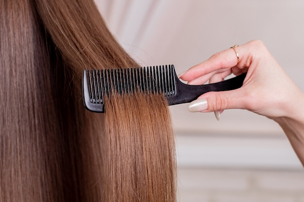 Парикмахеры расчесывают длинные волосы брюнетки в салоне красоты