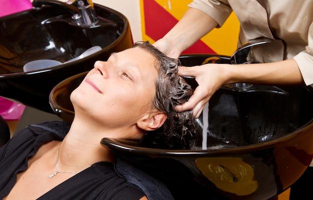 サロンで女性客の髪を手洗いする美容師