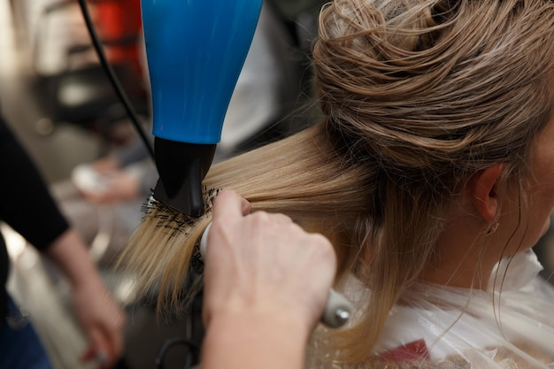 헤어 드라이어와 둥근 브러시로 금발 머리를 건조하는 미용사 손