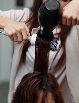 헤어 드라이어와 둥근 브러시로 갈색 머리를 건조하는 미용사 손