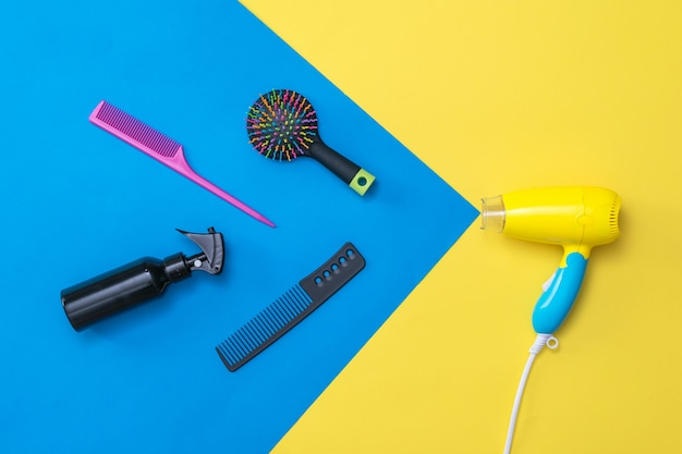 Hairdressing accessories flying out of the hair dryer. devices for drying hair on a colorful surface.