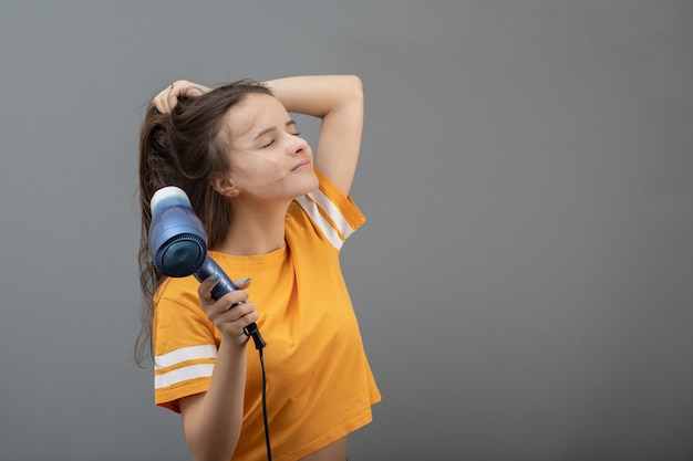 Hairdressing and beautiful styling. young caucasian woman dries hair with a hairdryer