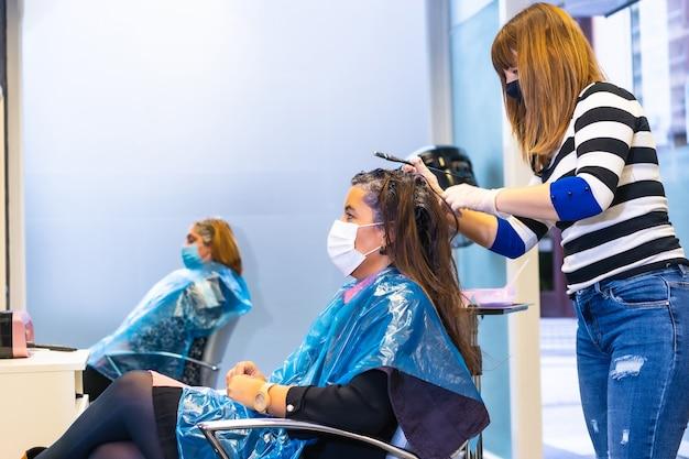 マスクと新しい通常の仕事をしている美容院。 covid-19パンデミック、コロナウイルスにおける美容師のセキュリティ対策