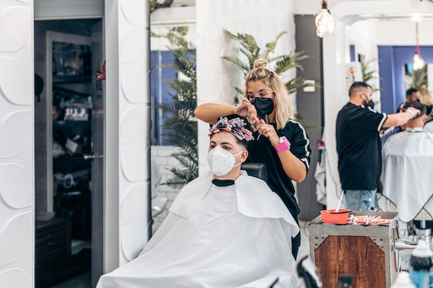 Парикмахерская с двумя работницами, стригущими и укладывающими волосы двум клиентам, сидящим на стуле.