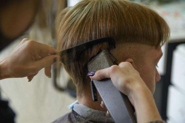 理髪サービス。男が理髪店の美容師スタイリストで髪を切った。はさみの櫛、クリッパーのクローズアップ。髪をカットを閉じます。