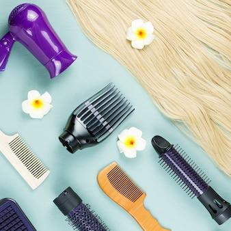 理髪ツールと青い木製のヘアエクステンション。トップビュー、フラットレイアウト