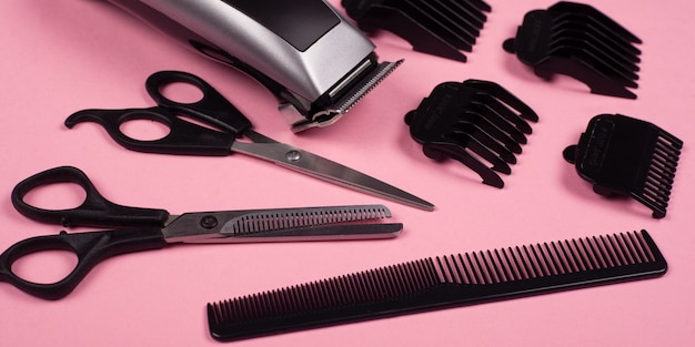 Hairdressing tools on a pink background, hair clipper, straight and thinning barber scissors and comb.