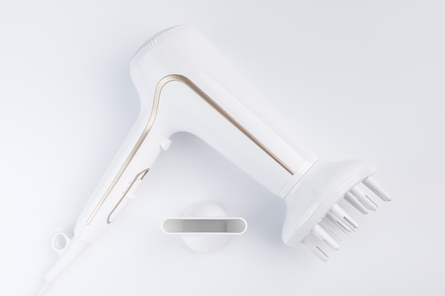 흰색 배경에 스타일링을 위해 확산 및 평면 노즐로 머리카락을 건조시키는 헤어 드라이어. 평면도.