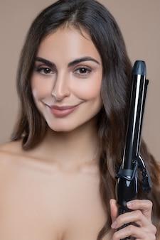 Прическа, длинные волосы. красивая молодая темноволосая женщина с карими глазами с плойкой, делающей кудри для себя