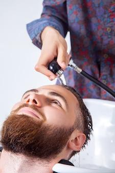 ヘアスタイリング。散髪の準備をしている間、理髪店で彼のクライアントの頭を洗う理髪店のトリミングされた画像
