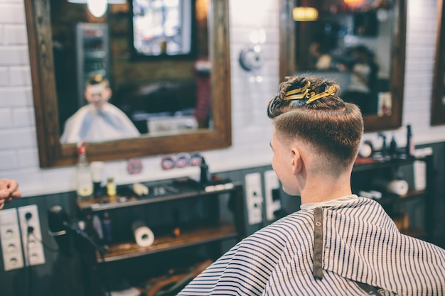 Клиент-парикмахер и мужчина с прической смотрят в зеркало