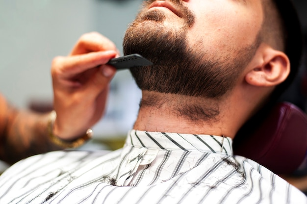 Hairstylist combing customer beard