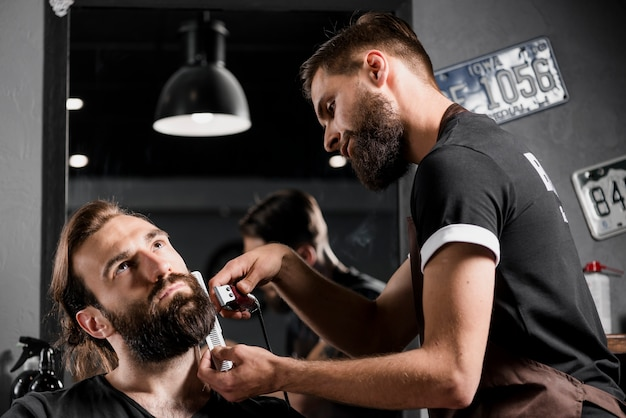 Hairstylist cutting man's beard in barber shop