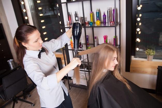 サロンでヘアドライヤーでブロンドの髪を乾燥させるヘアスタイリスト