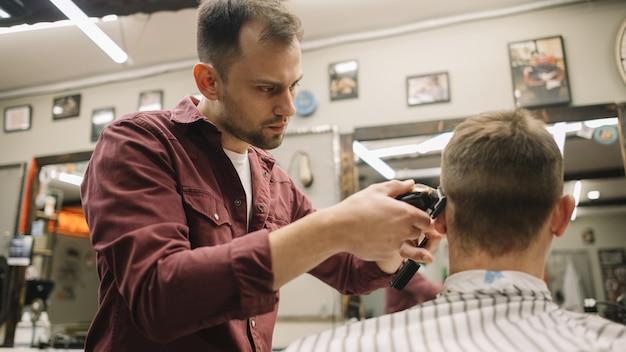 理髪店で散髪を与えるヘアスタイリスト