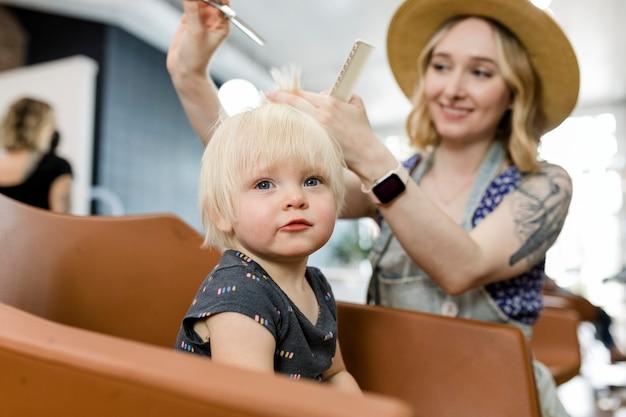 小さな子供に散髪をするヘアスタイリスト