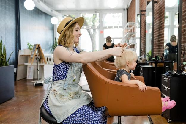 Hairstylist giving a little kid a haircut