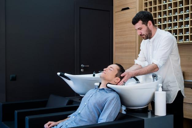 Парикмахер парикмахерская мытье волос клиента - молодой человек, расслабляющий в парикмахерской салон красоты