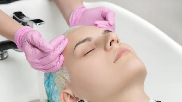 Руки парикмахера в розовых перчатках моют волосы изумрудного цвета в профессиональном салоне красоты.