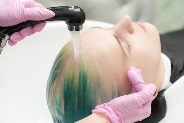 헤어스타일리스트의 손은 고객의 긴 머리를 녹색과 변색된 머리카락으로 세면대에서 샤워기의 물로 씻습니다. 미용실에서 분홍색 보호 장갑을 끼고 일하는 미용사.