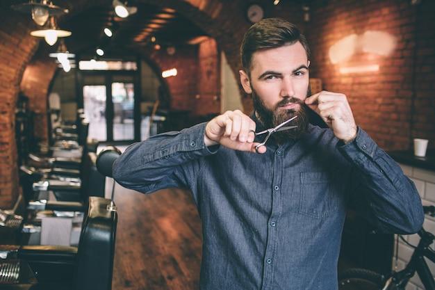 Парикмахер стоит в парикмахерской и стриг ножницами собственную бороду. он держит одну часть своих усов одной рукой и смотрит в камеру.