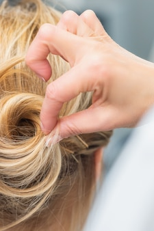 Hairstylist making bride wedding hairstyle